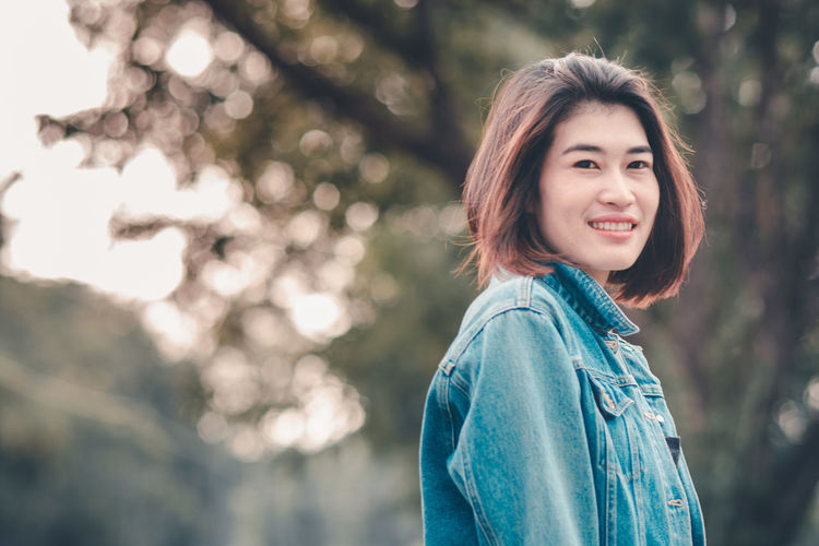 Asian Woman Asian Girl Asian Teen Beautiful Woman Beauty Casual Clothing Focus On Foreground Hairstyle Happiness Leisure Activity Lifestyles Looking At Camera Nature One Person Outdoors Portrait Real People Smiling Standing Warm Clothing Women Young Adult Young Women