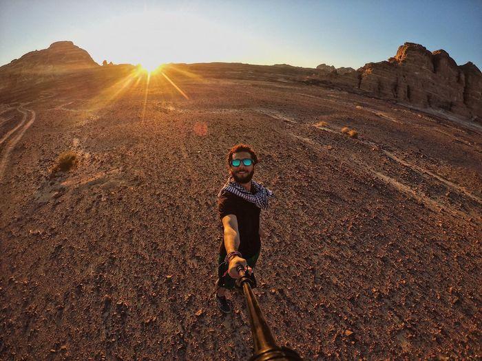 Portrait of man on field in desert against sky