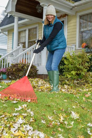 Woman holding umbrella standing in yard