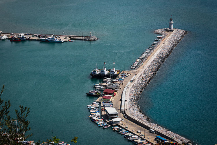 Top view of a pier with a beautiful white lighthouse and a pier with many boats and yachts