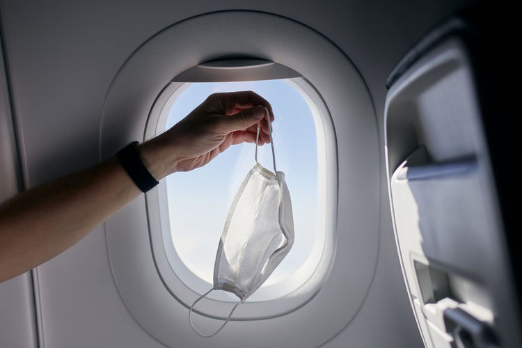 Hand holding protective face mask against airplane window.