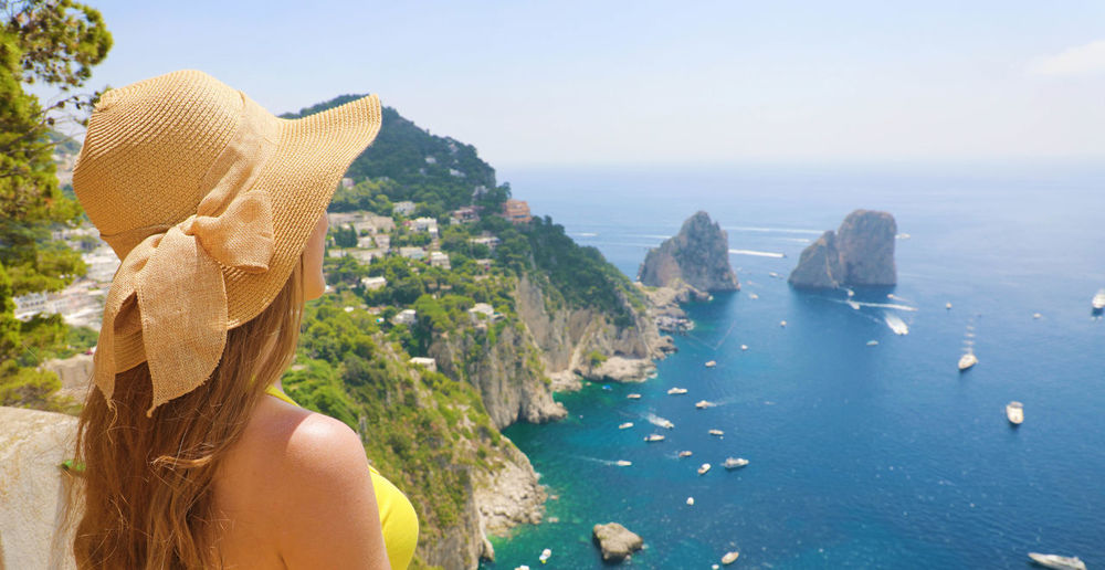 Beautiful girl in Capri, Italy Water One Person Leisure Activity Real People Nature Lifestyles Women Outdoors Seascape Woman Girl Back View Of Girl Rear View Faraglioni Faraglioni Capri Woman With Hat Girl With Hat Italy Paradise Blue Sea Woman Hat Faraglioni Rocks Pathway Take Picture Hiker