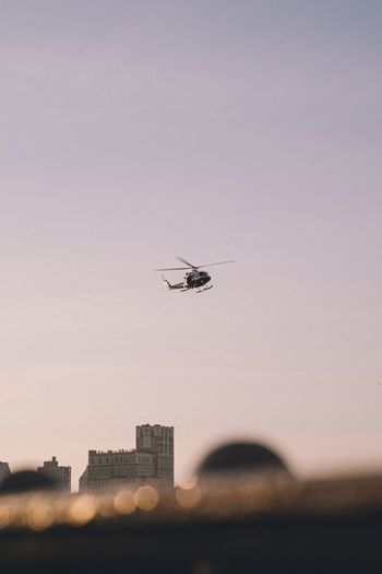 Helicopter flying over buildings in city