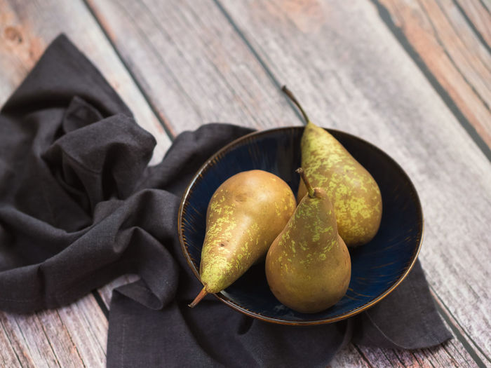 Conference Pears Food Food And Drink Freshness Healthy Eating Table Wellbeing Still Life Wood - Material Fruit No People Close-up High Angle View Bowl Pear Indoors  Focus On Foreground Group Of Objects Green Color Day Textile Ripe