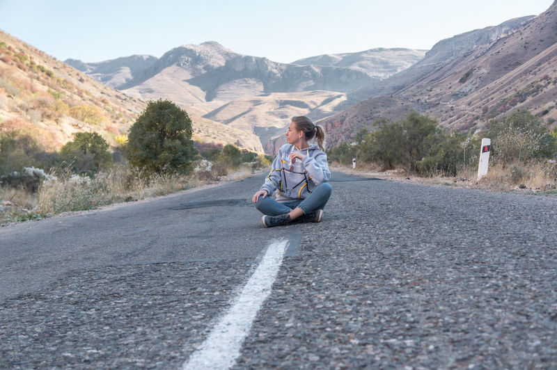 Side view of man sitting on road