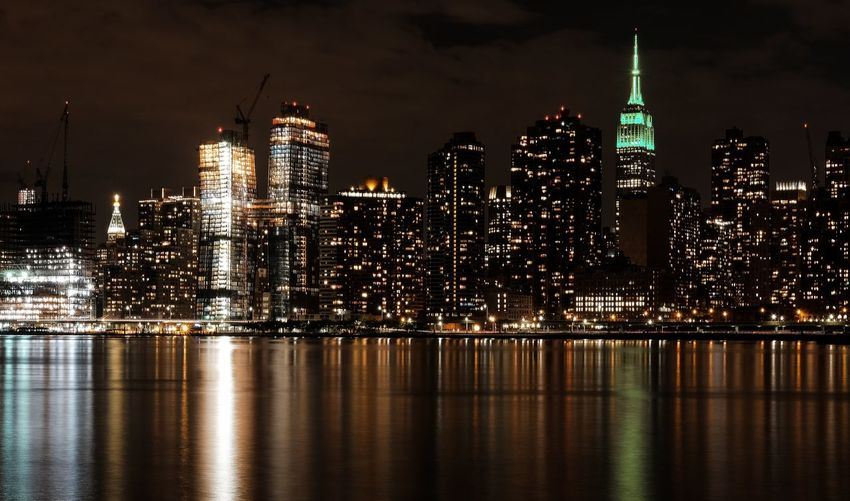 Illuminated empire state building by east river against sky in manhattan at night