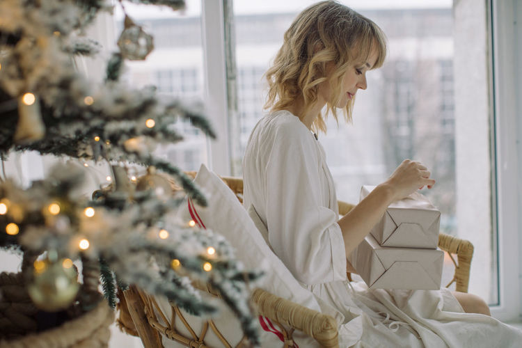 Woman looking at packages while sitting by christmas tree at home
