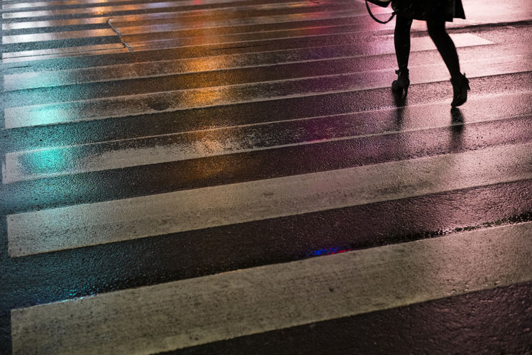 Low Section Of Silhouette Woman Walking On Wet Street In City At Night