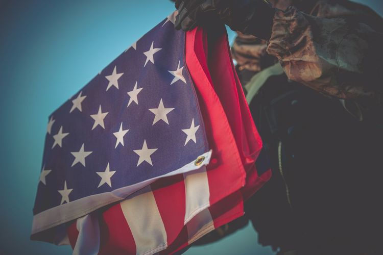 Midsection Of Person Holding American Flag