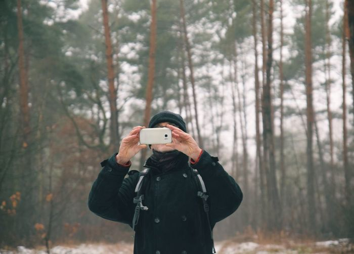 Man photographing through camera in forest