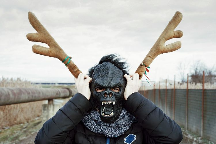 Close-up of man wearing gorilla mask against sky