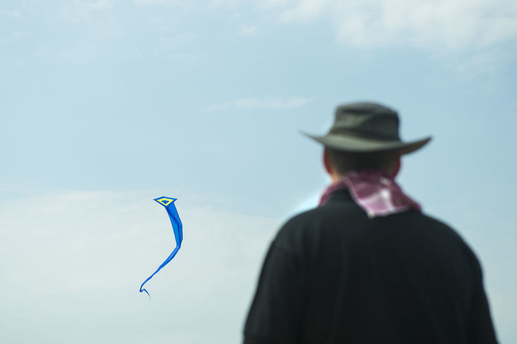Rear view of man looking at kite against sky