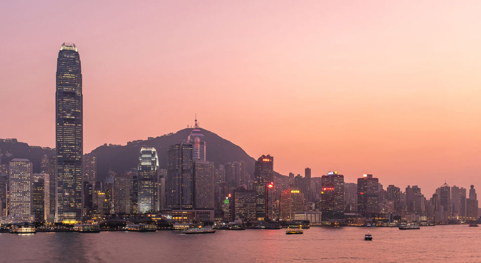 Hong kong cityscape at sunset, long exposure photography for boat movement
