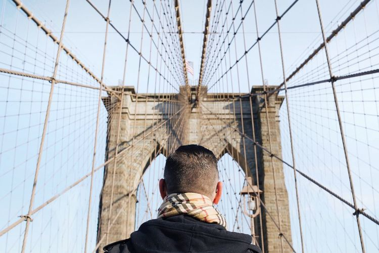 Rear view of man on brooklyn bridge against clear sky