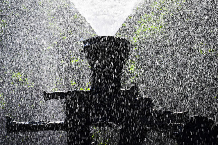 Blurred motion of man standing on wet fence during rainy season