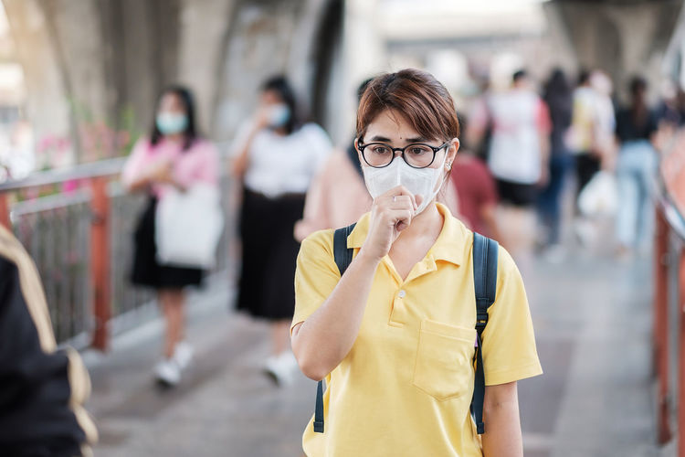 Woman coughing while wearing pollution mask