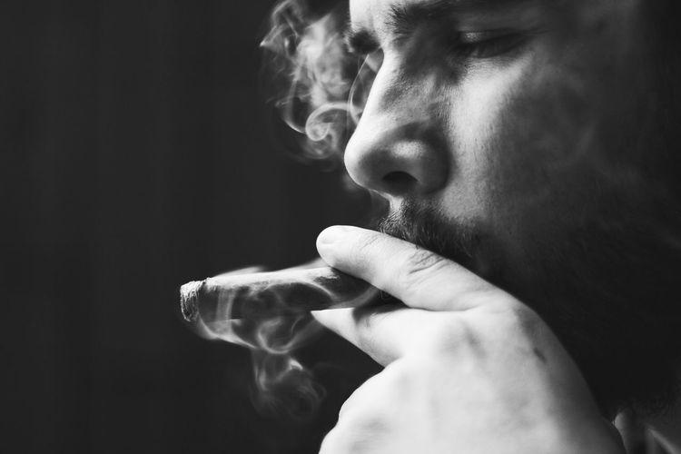 Close-up of young man smoking cigar