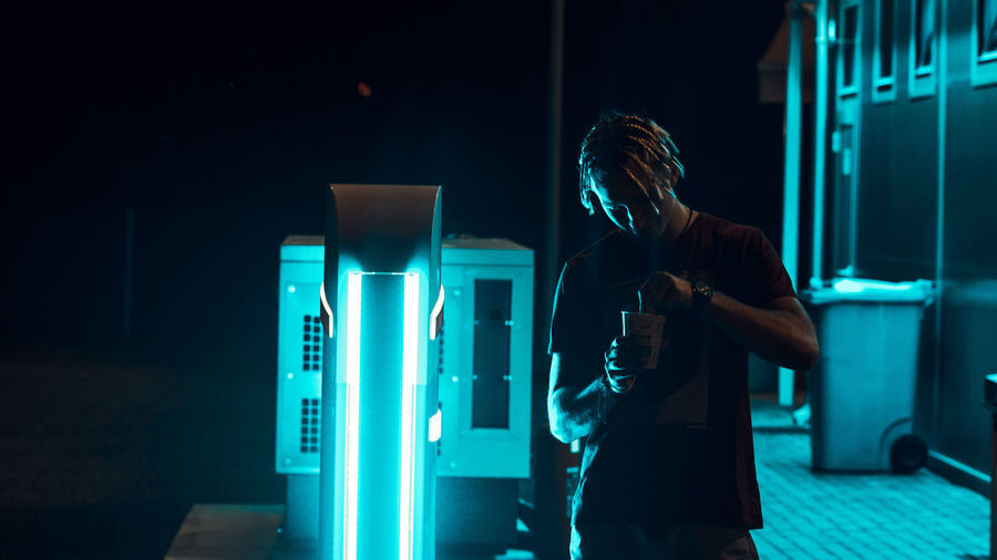Man Having Drink While Standing By Illuminated Lighting Equipment