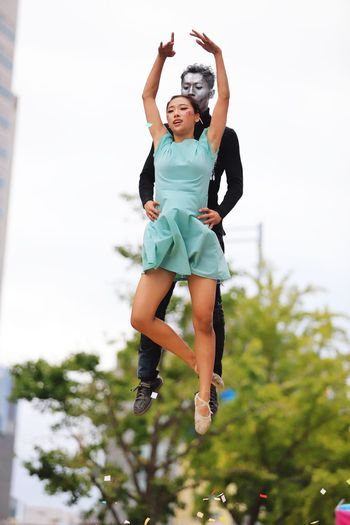 Low Angle View Of Man And Woman Levitating Against Sky