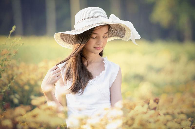 Beautiful young woman wearing hat standing outdoors