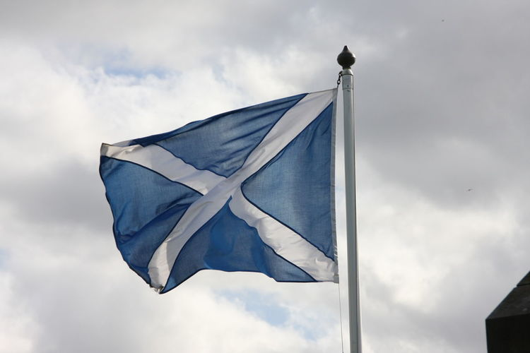 Low angle view of scottish flag waving against sky