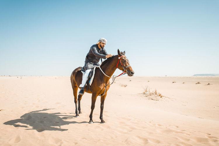 Man riding horse on sand