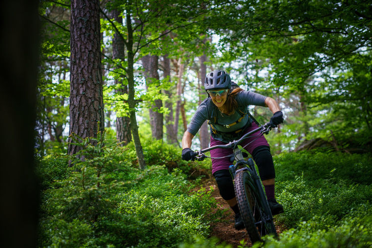 Woman riding mountain bike on footpath amidst trees in forest, austria
