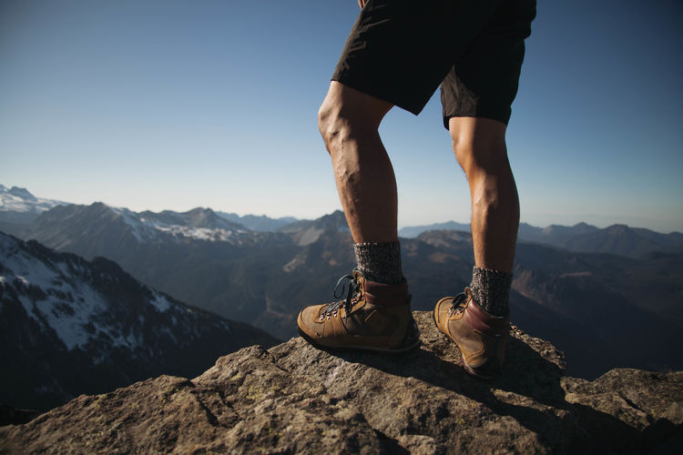 Low section of man standing on mountain against sky