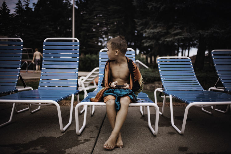 Boy sitting on lounge chair at poolside