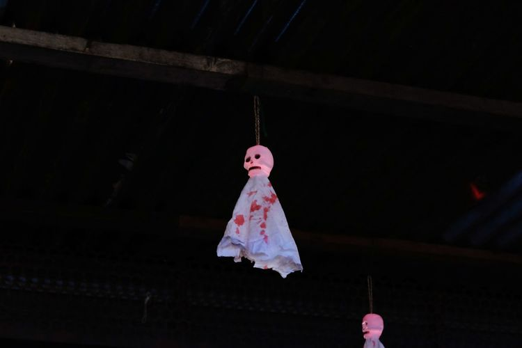 Low angle view of pink decoration hanging at night