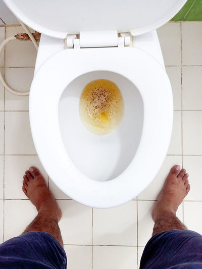 Person standing pee down in the toilet
