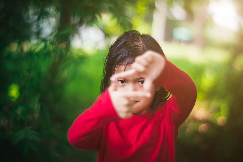 Portrait of little girl make a framing with her hands while playing the the woods. Adorable Asian  Beauty In Nature Blur Bokeh Child Childhood Close-up Cute Day Funny Girl Happiness Happy Headshot Little Looking At Camera Malaysia Nature Outdoors People Portrait Red Shallow Depth Of Field Water EyeEmNewHere