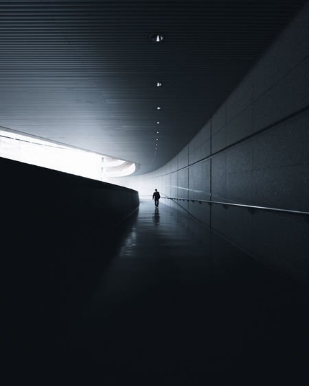 Mid distance of silhouette man walking in tunnel