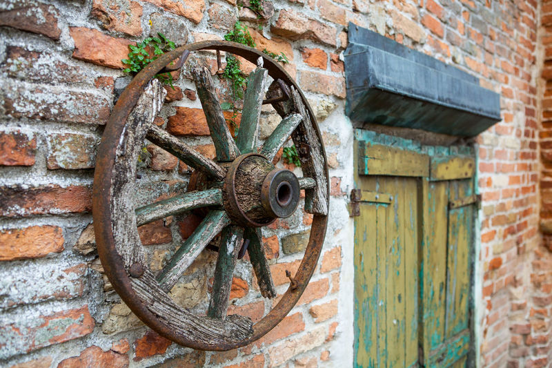 Wooden chariot wheel Chariot Wheel Country Wheel Wood Abandoned Architecture Bad Condition Brick Wall Building Exterior Built Structure Close-up Damaged Day Door No People Outdoors Red Brick Wagon Wheel Wall - Building Feature Wheel Wooden