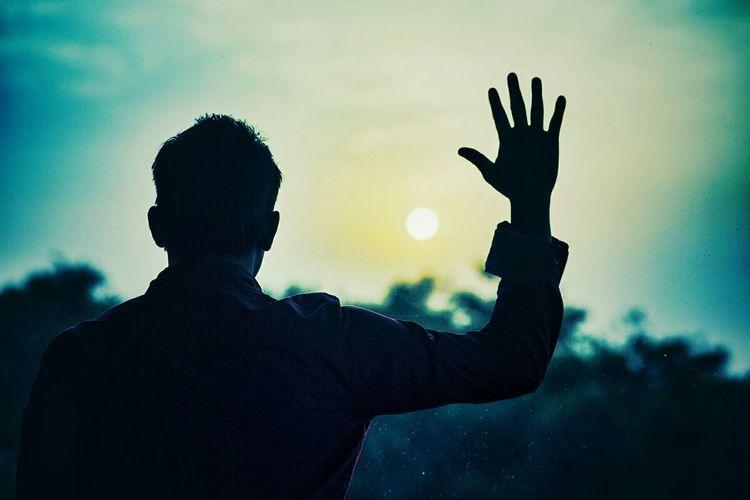 Silhouette Man Raising Hand Against Sky At Sunset