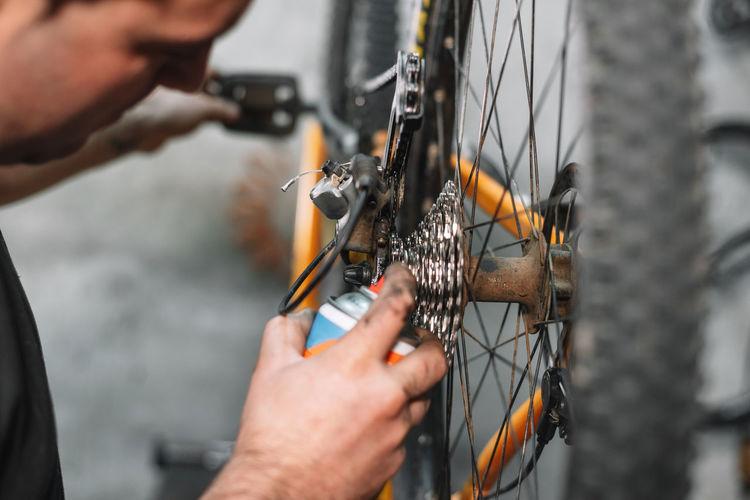 Cropped image of man repairing bicycle at workshop