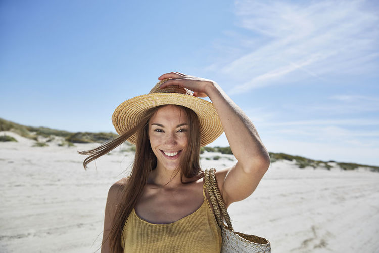 Portrait of smiling young woman wearing hat on beach