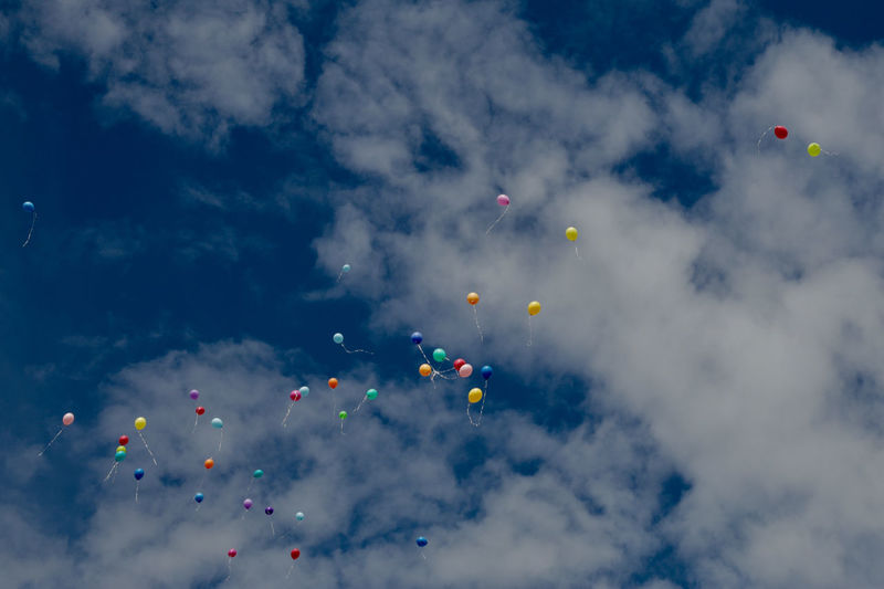 Low angle view of helium balloons flying in cloudy sky