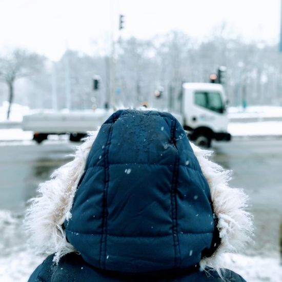 Rear view of person standing outdoors during winter