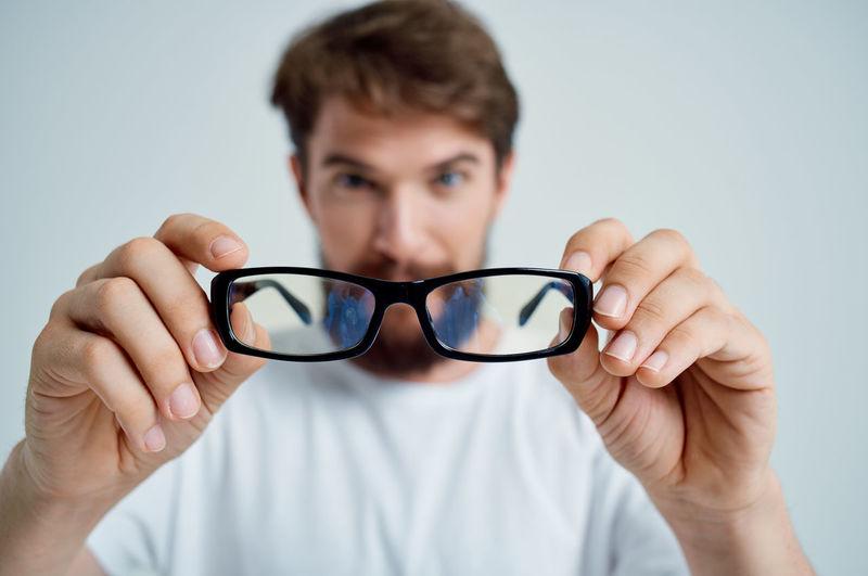 Close-up portrait of man holding eyeglasses against white background