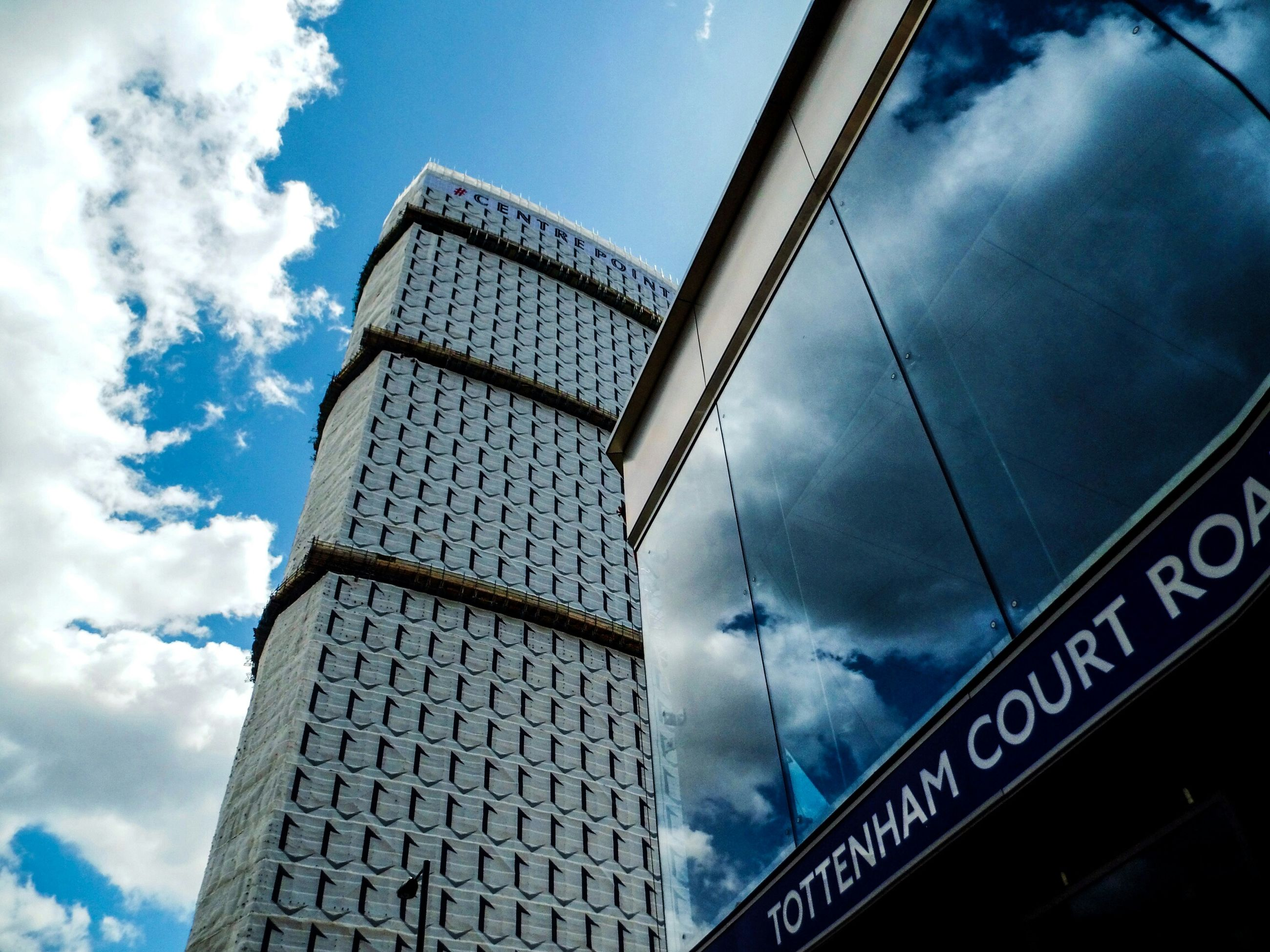 low angle view, sky, architecture, built structure, cloud - sky, building exterior, cloudy, cloud, modern, tower, building, day, city, tall - high, outdoors, blue, no people, architectural feature, office building, reflection
