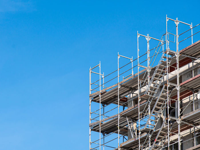 Low angle view of modern building under construction against clear blue sky