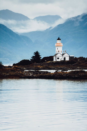 Lighthouse by lake and buildings against sky