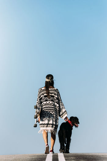 Rear view of woman with dog against clear sky