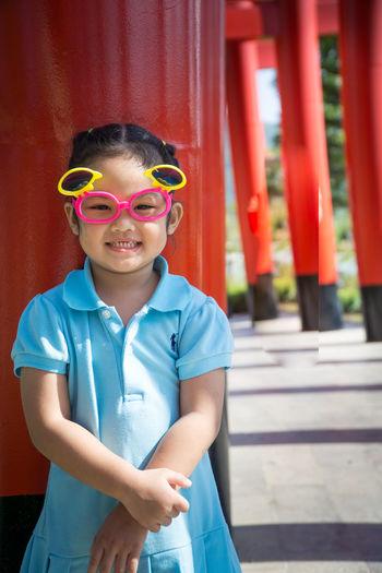 Portrait of girl wearing sunglasses standing torii