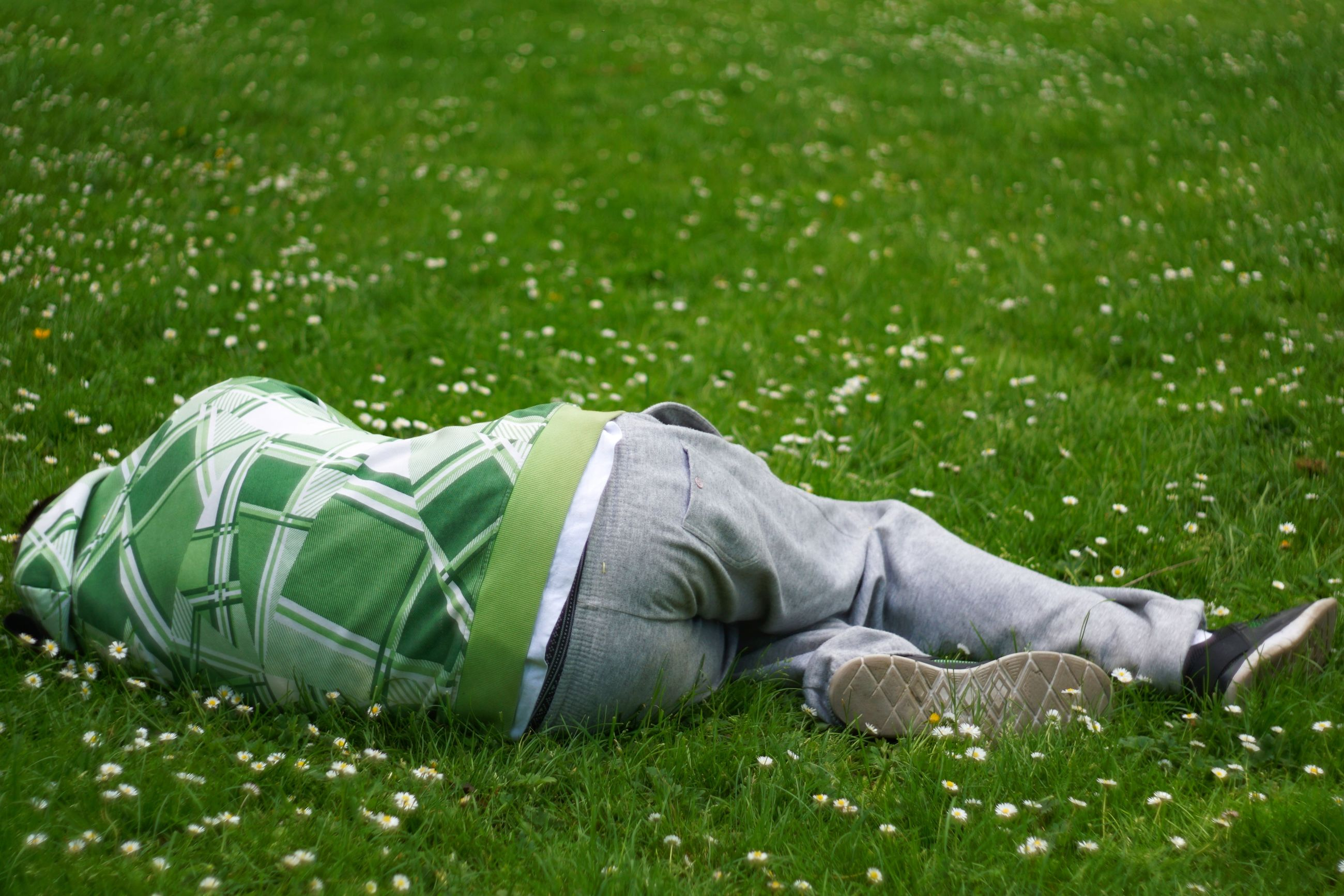grass, lying down, plant, relaxation, one person, nature, sleeping, day, green color, tired, lying on back, men, exhaustion, field, lawn, resting, adult, land, casual clothing, napping, uniform
