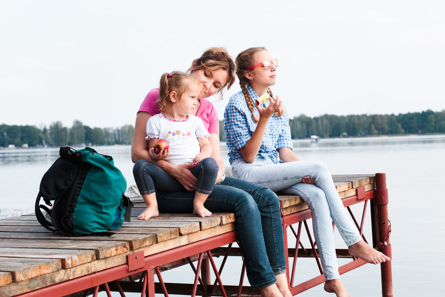 Family spending vacation time together having a snack sitting on jetty over the lake on sunny day in the summertime Children Family Moments Mother Recreation  Relaxing Summertime Vacation Time Vacations Childhood Family Time Girl Joy Joy Of Life Lake Leisure Leisure Activity Lifestyles Outdoors Real People Recreational Pursuit Relaxation Relaxing Time Summer Summer Vibes
