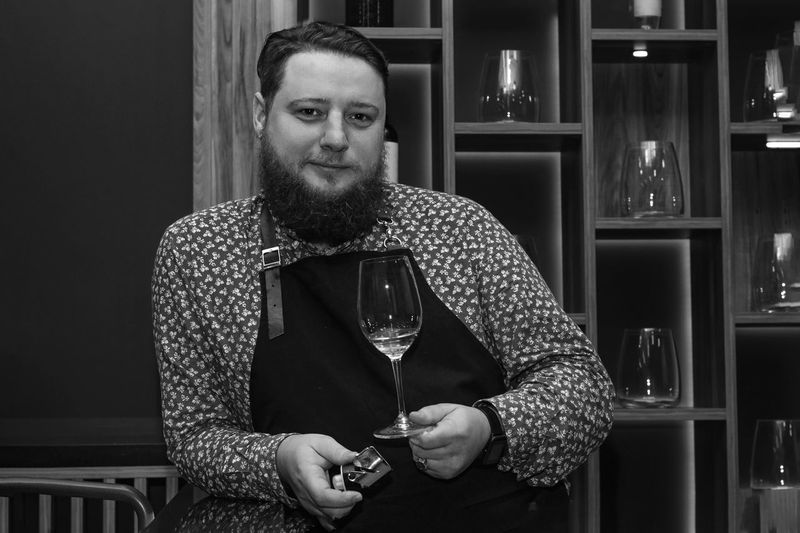 Portrait of man holding wineglass while standing in restaurant