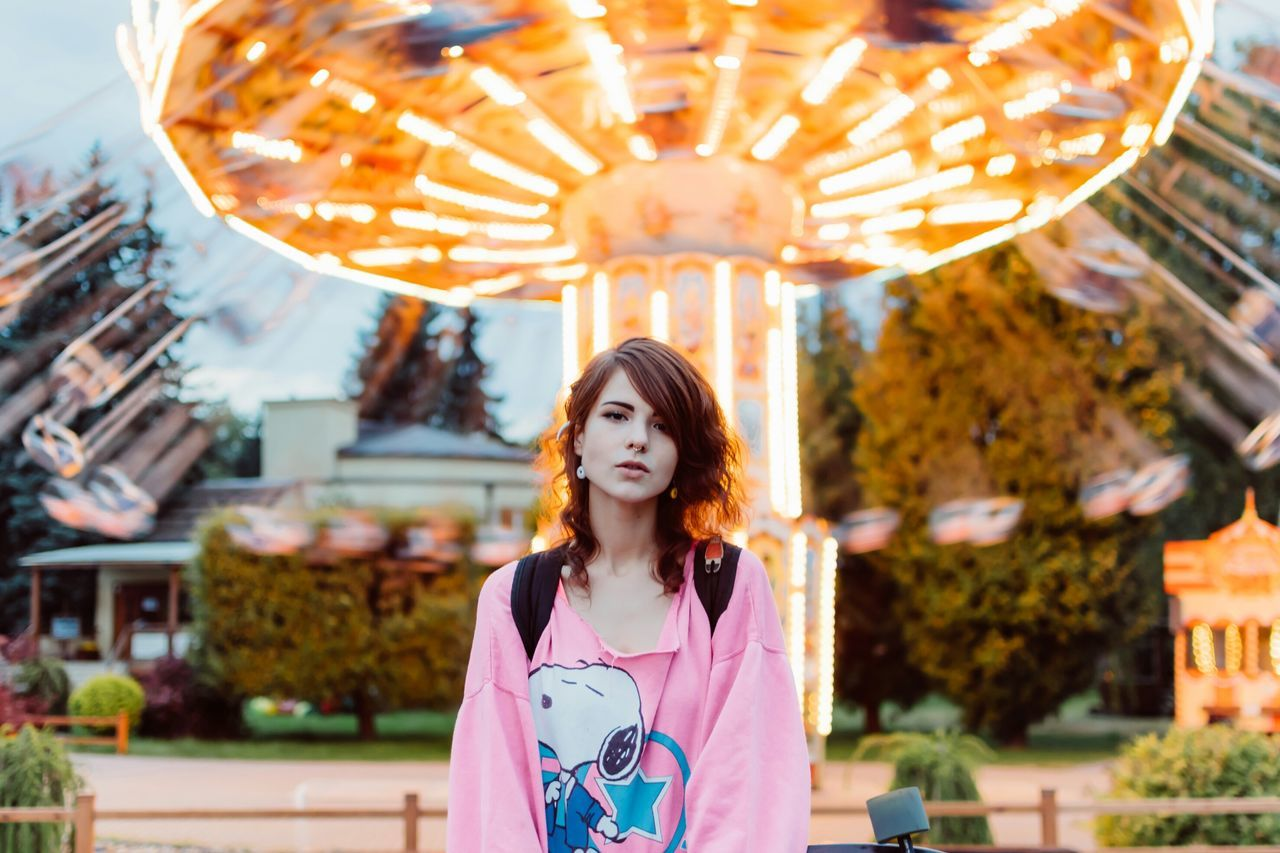 Portrait of young woman standing against illuminated carousel
