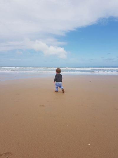 Rear view of boy walking at beach against sky